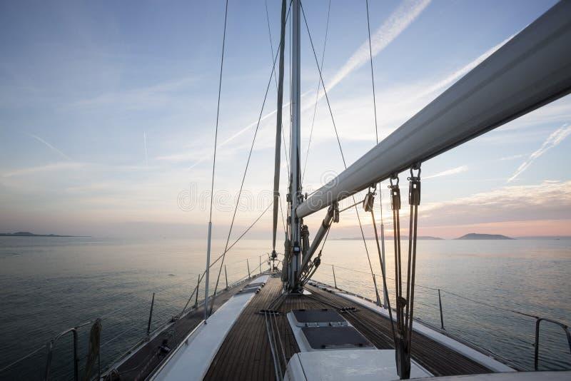Navegación de lujo del barco de vela en el mar durante puesta del sol imagenes de archivo