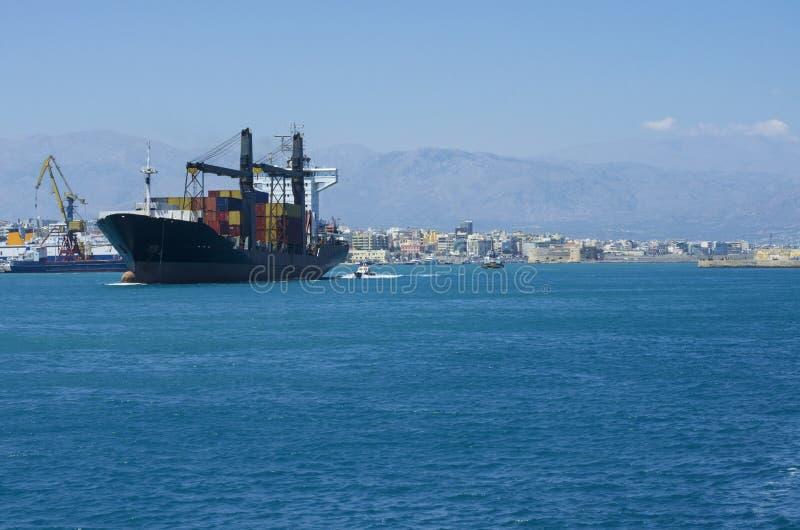 Navegación de portacontenedores de la bahía de Heraklion, acompañada por una nave experimental imagen de archivo libre de regalías