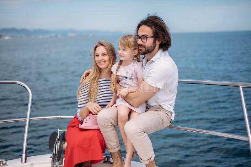 Navegación del padre, de la madre y de la hija en el yate en el mar imagen de archivo libre de regalías