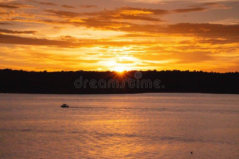 Navegación en la puesta del sol en el gran río imágenes de archivo libres de regalías