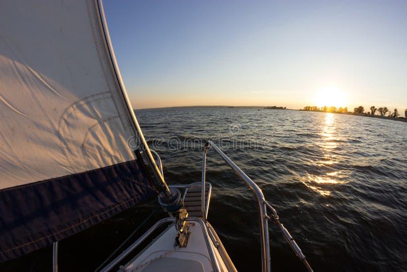 Navegación en la puesta del sol Una visión desde la cubierta del yate al arco y a las velas foto de archivo
