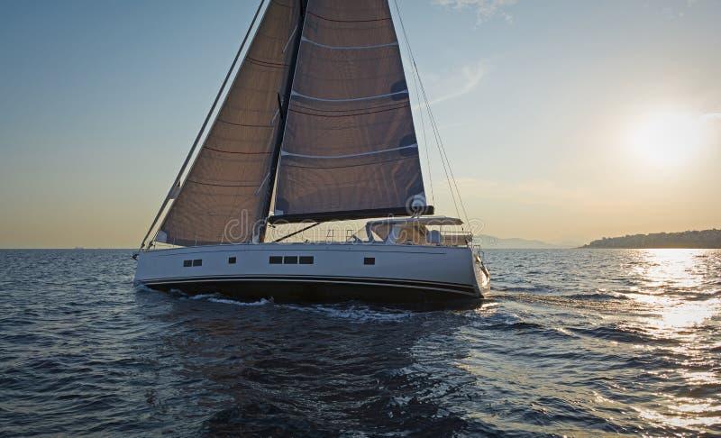 Navegación en la puesta del sol Yate moderno de la navegación imagen de archivo libre de regalías