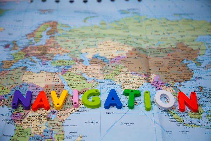 Navegación escrita con los bloques del juguete en un mapa del mundo imagen de archivo libre de regalías