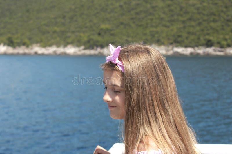 Navegación feliz de la niña en un barco que sonríe en el mar en travesía del verano imagenes de archivo