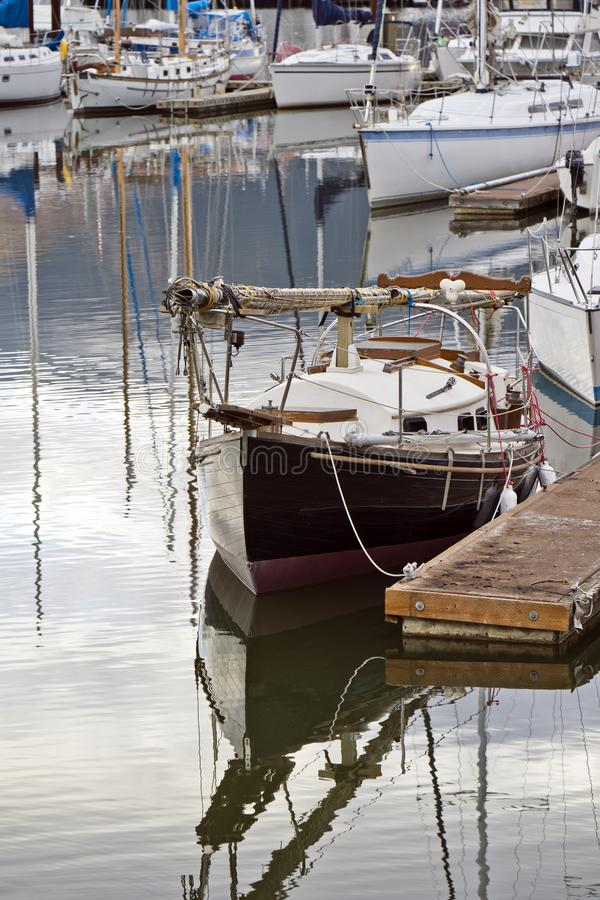 Navegando el yate con el palo doblado y las cabinas amarradas al embarcadero al lado de otros yates en el puerto imagenes de archivo