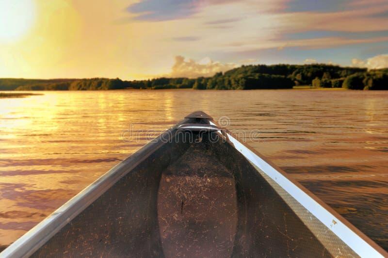 Navegue por puesta del sol en un lago foto de archivo