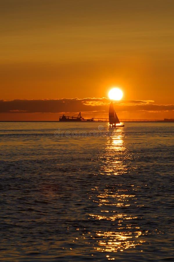 Navegue y envíe en la puesta del sol en el Océano Pacífico foto de archivo