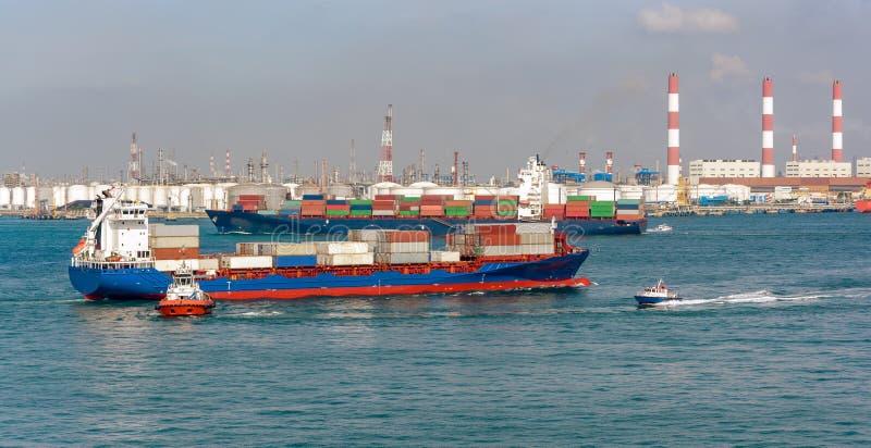 Naves y barcos delante de un terminal del almacenamiento de aceite foto de archivo libre de regalías