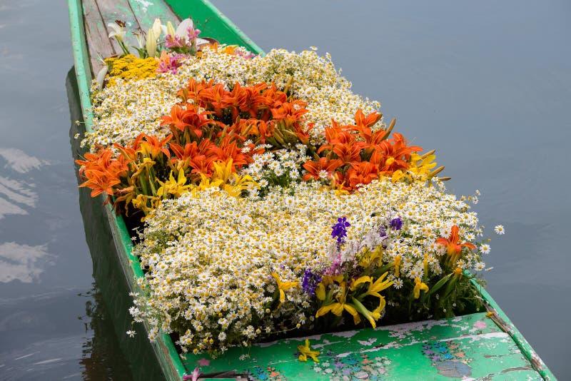 Navi e fiori su Dal Lake a Srinagar L'India immagini stock