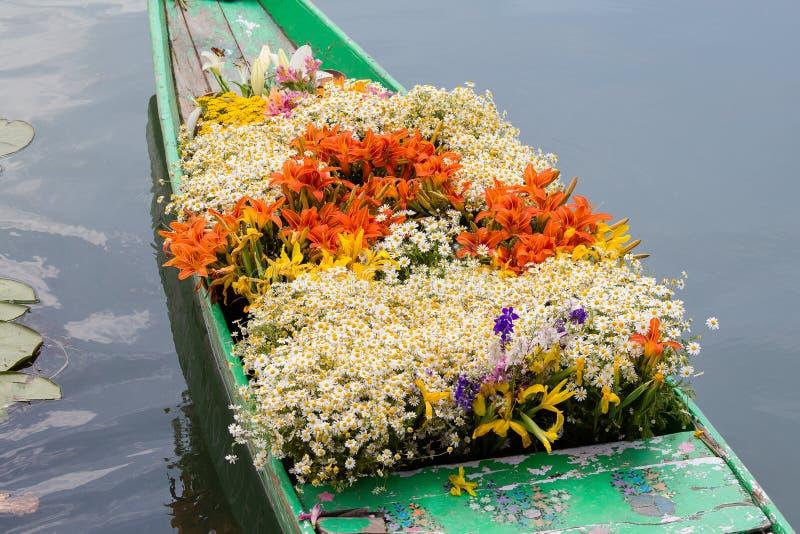 Navi e fiori su Dal Lake a Srinagar L'India immagine stock libera da diritti