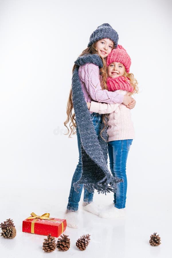 Navidad Año Nuevo Dos pequeñas hermanas que se sostienen presentes en ropa del invierno Sombreros y bufandas rosados y grises Fam imagen de archivo