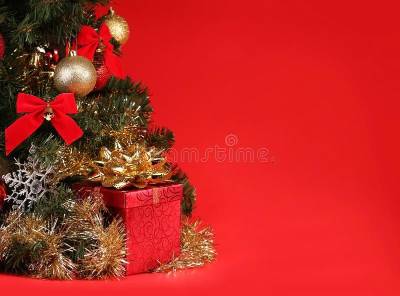 Navidad Caja de regalo debajo del árbol de navidad sobre fondo rojo imagenes de archivo