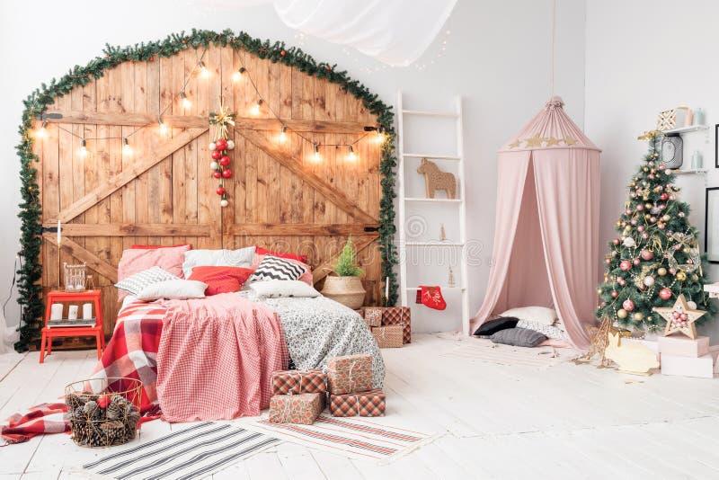 Navidad en dormitorio de la mañana Cama matrimonial en interior de la Navidad en el fondo de madera de la pared foto de archivo