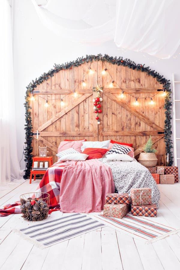 Navidad en dormitorio de la mañana Cama matrimonial en interior de la Navidad en el fondo de madera de la pared foto de archivo libre de regalías