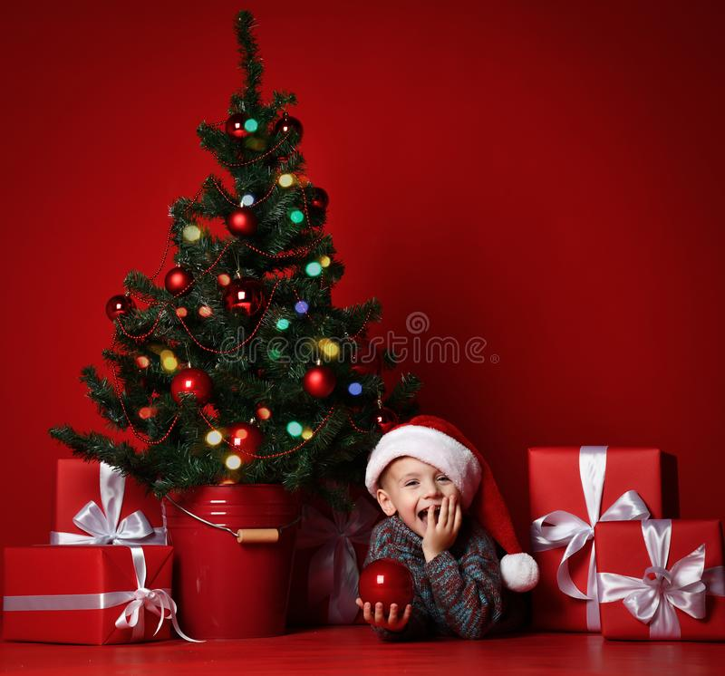Navidad feliz y Año Nuevo Retrato del niño en regalos de la Navidad del sombrero rojo de Papá Noel que esperan para imagen de archivo