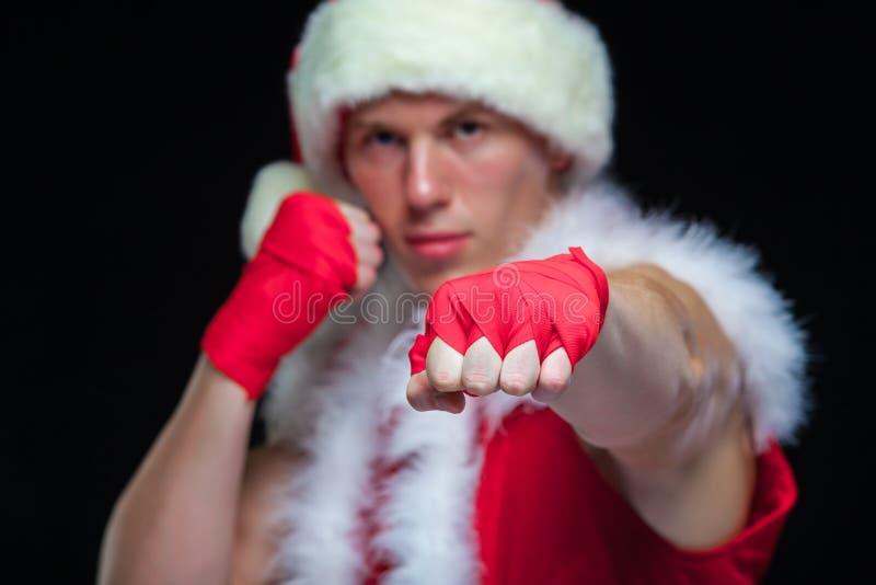 Navidad Kickbox muscular del combatiente que encajona a Santa Claus With Red Bandages aislada en fondo negro foto de archivo libre de regalías