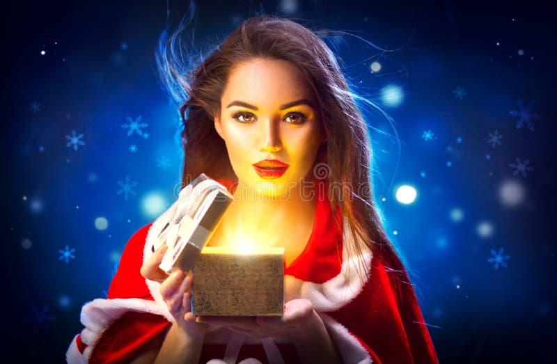 Navidad Mujer joven morena de la belleza en caja de regalo de la abertura del traje del partido sobre fondo de la noche del día d foto de archivo