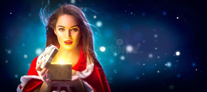 Navidad Mujer joven morena de la belleza en caja de regalo de la abertura del traje del partido sobre fondo de la noche del día d fotos de archivo