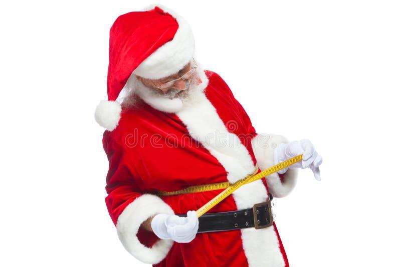 Navidad Santa Claus está midiendo la cintura con una cinta El concepto de pérdida de peso, consumición sana Aislado en blanco fotos de archivo