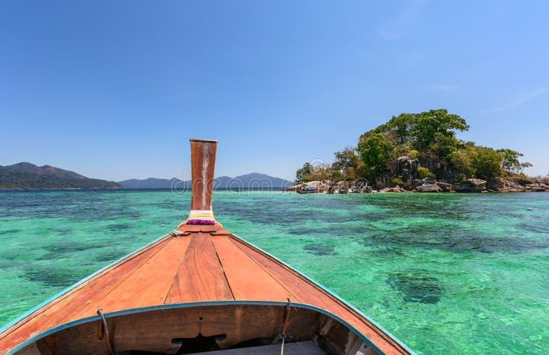 Navigação de madeira do barco da longo-cauda no mar esmeralda imagens de stock