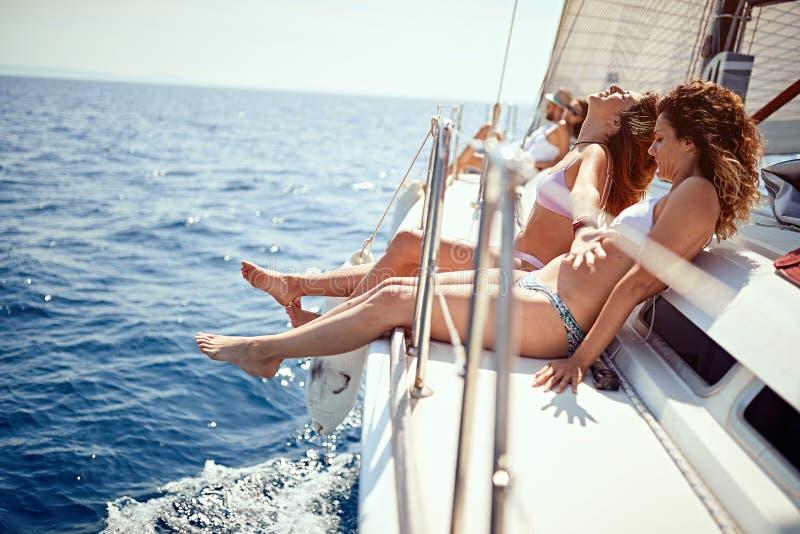 Navigação de sorriso no iate - férias, curso, mar, amizade e pessoa dos amigos fotografia de stock