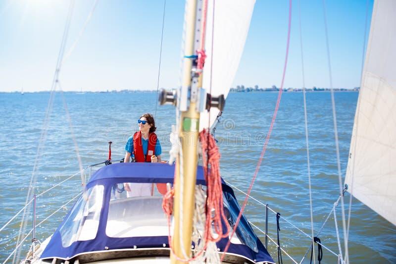 Navigação do homem novo Menino do adolescente no barco de vela do mar foto de stock