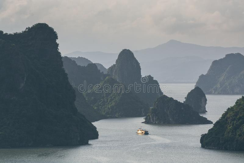 Navigação do navio de cruzeiros do turista entre montanhas da pedra calcária na baía de Halong, Vietname imagem de stock