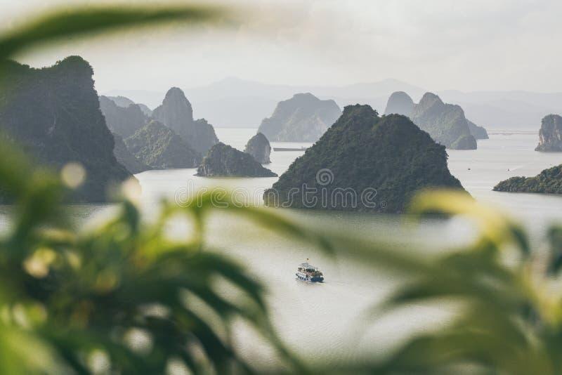Navigação do navio de cruzeiros do turista entre montanhas da pedra calcária na baía de Halong, Vietname foto de stock