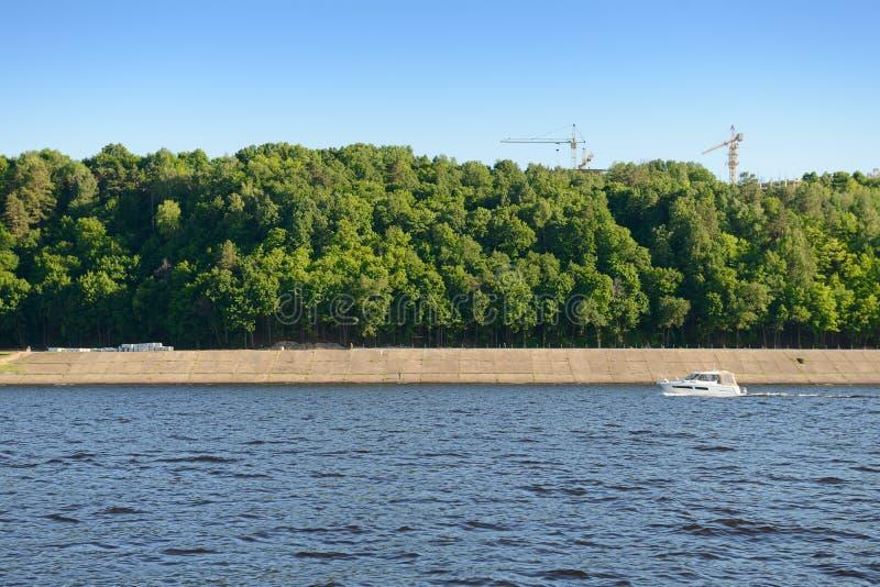 Navigação do Powerboat abaixo do rio ao longo de uma terraplenagem concreta com uma floresta verde e os guindastes de torre imagem de stock royalty free
