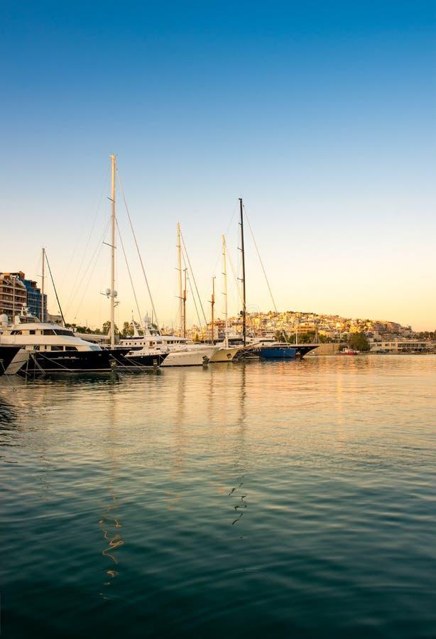 A navigação e o luxo viajam de automóvel iate no porto de Zeas Por do sol e v imagem de stock royalty free