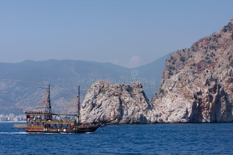 Navigação turística do barco pelo cabo Jilvarda da rocha do castelo de Alanya imagem de stock