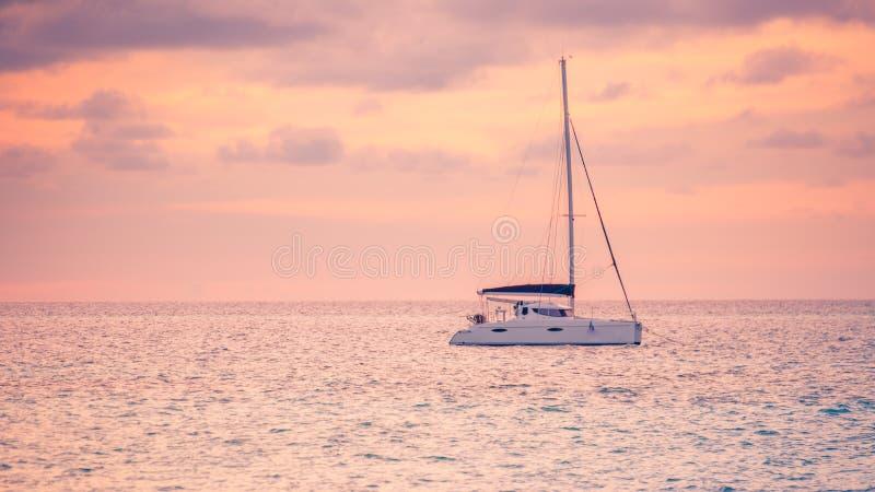 Navigando yacht nel mare al tramonto, tramonto tropicale del mare Sport e fondo ricreativo immagine stock libera da diritti