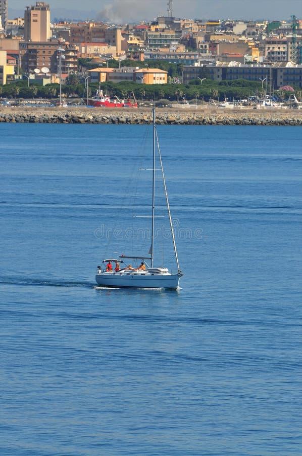 Navigation étroite de bateau près de marina de Cagliari photographie stock libre de droits
