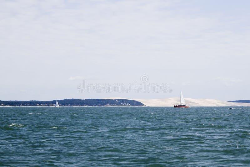 Navigation de bateau à voile devant la dune de Pilat photo stock