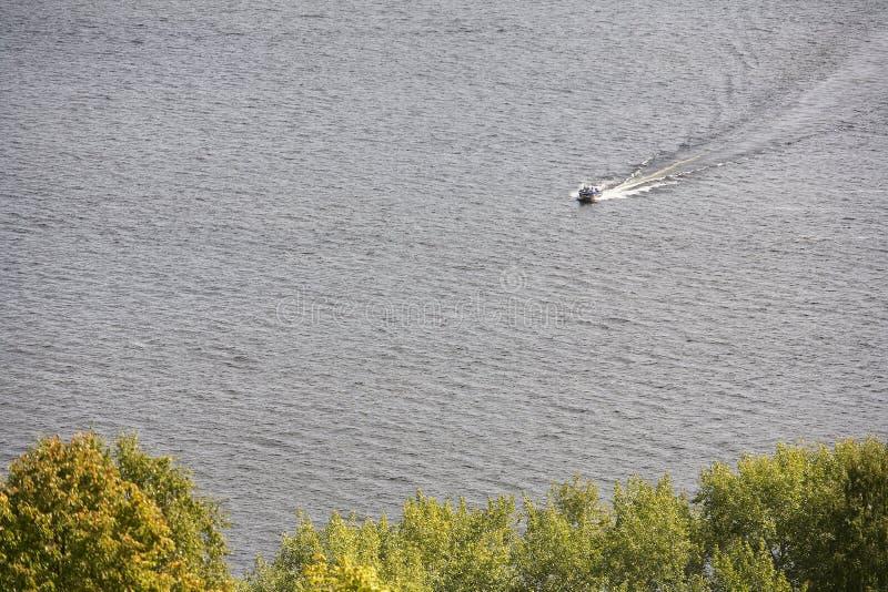 Navigation de petit bateau en bas de la rivière sur un fond des arbres photo libre de droits