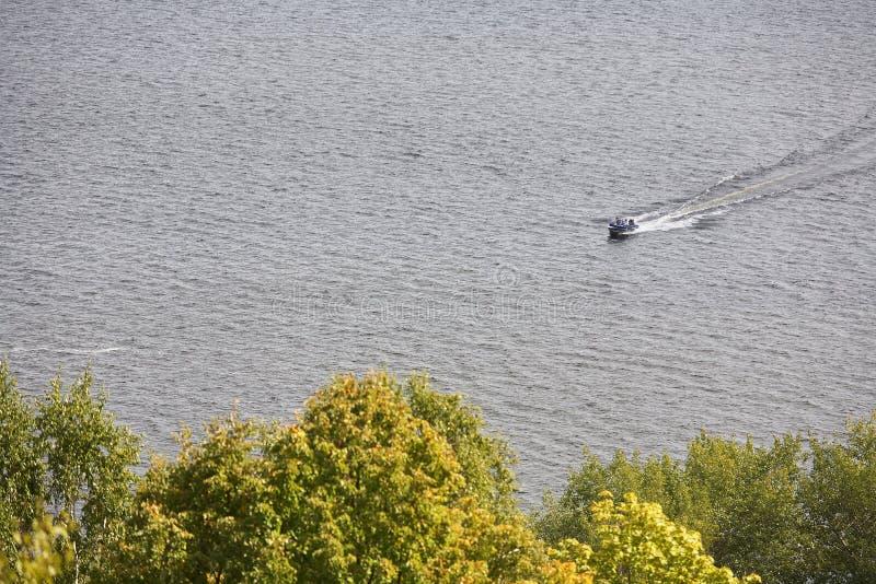 Navigation de petit bateau en bas de la rivière sur un fond des arbres images libres de droits