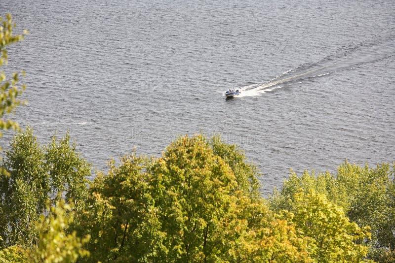 Navigation de petit bateau en bas de la rivière sur un fond des arbres photographie stock