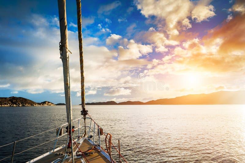 Navigation de yacht entre les îles en mer au coucher du soleil image stock