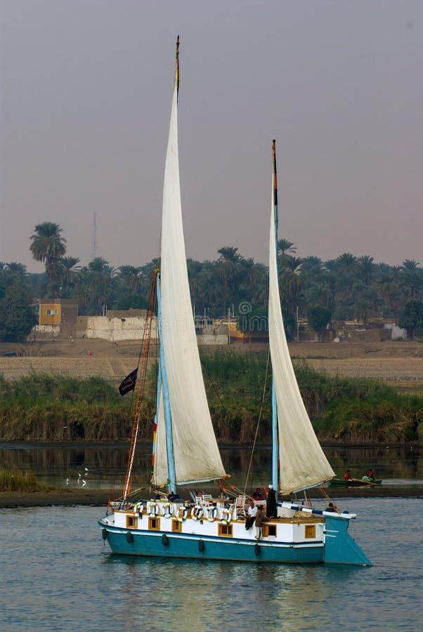 Navigation deux-mâtée typique de bateau le long de la rivière, près d'un petit village de hous très pauvre photo stock