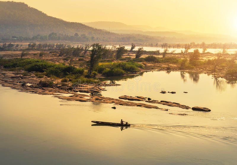 Navigation en bois de bateau de pêche dans le Mekong sur le lever de soleil à la frontière de la Thaïlande et du Laos photographie stock libre de droits