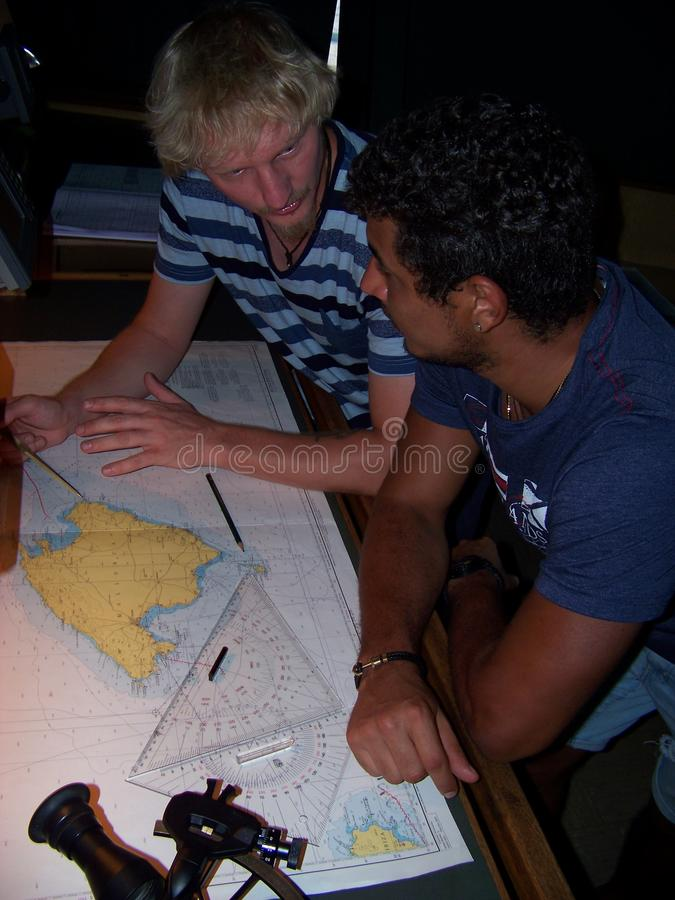 Navigational duty officer explaining to cadet how to insert the position into the sea chart stock images