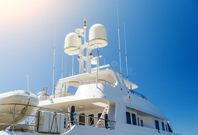 Navigationsausrüstung auf Dach der privaten Luxusyacht, zwei Bereichdetails weißer Yacht gegen blauen Himmel und der Sonne stockfotografie
