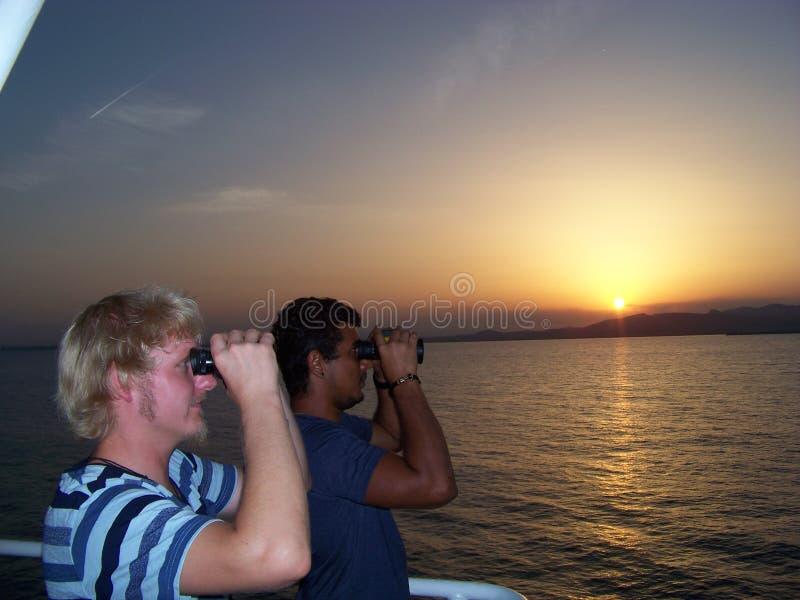 Navigationsoffizier passt die Peripherie des Anchorages mit jungem Auszubildendem auf stockfoto