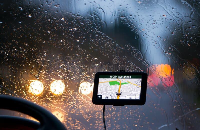 Navigatore di GPS in vetro di pioggia e fari dei fanali posteriori fotografia stock libera da diritti