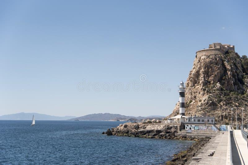 Navigazione della barca a vela accanto al faro di Aguilas in Spagna fotografie stock