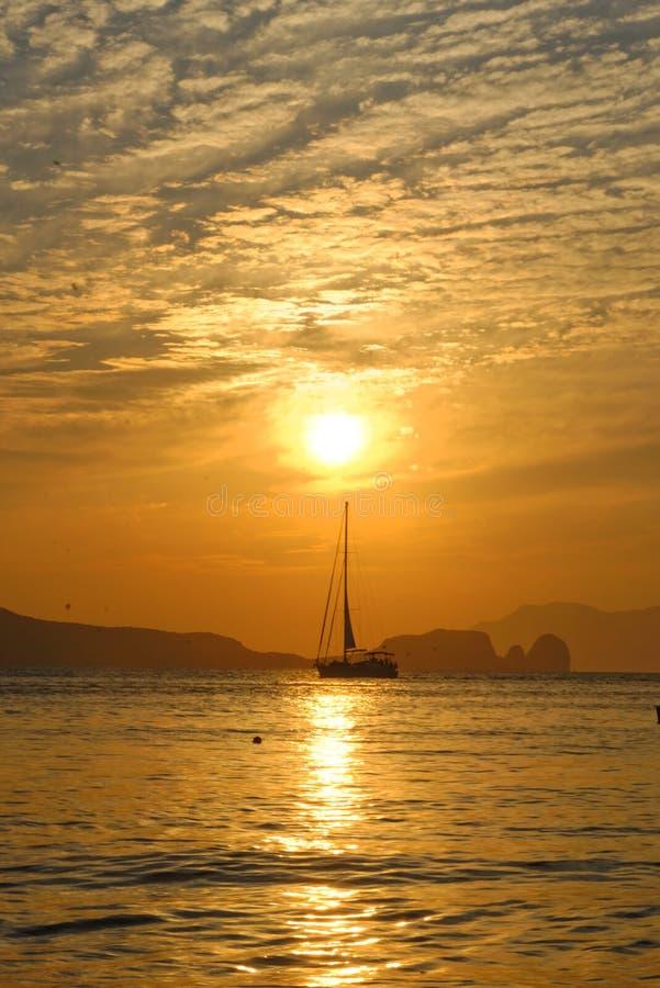 Navigazione della barca a vela al tramonto immagine stock