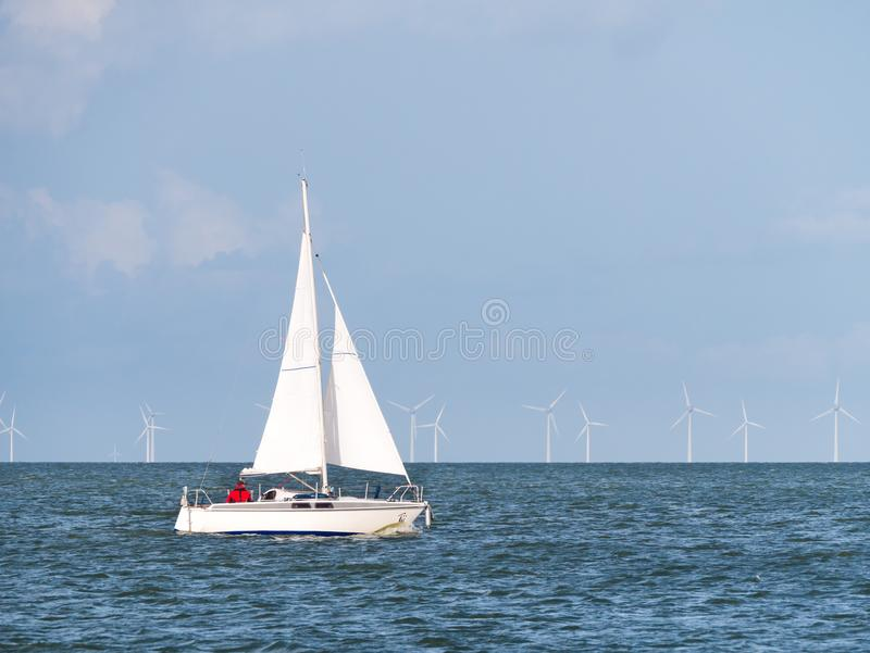 Navigazione della barca a vela sul lago IJsselmeer e sui windturbines del parco eolico fotografie stock libere da diritti