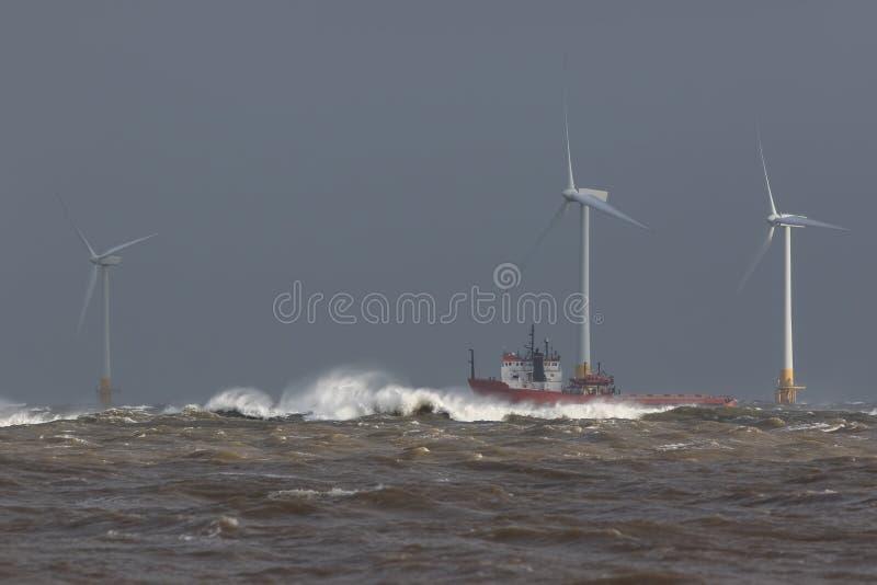 Navigazione della nave in mare agitato intorno alle turbine dell'azienda agricola di vento di terra fotografia stock libera da diritti