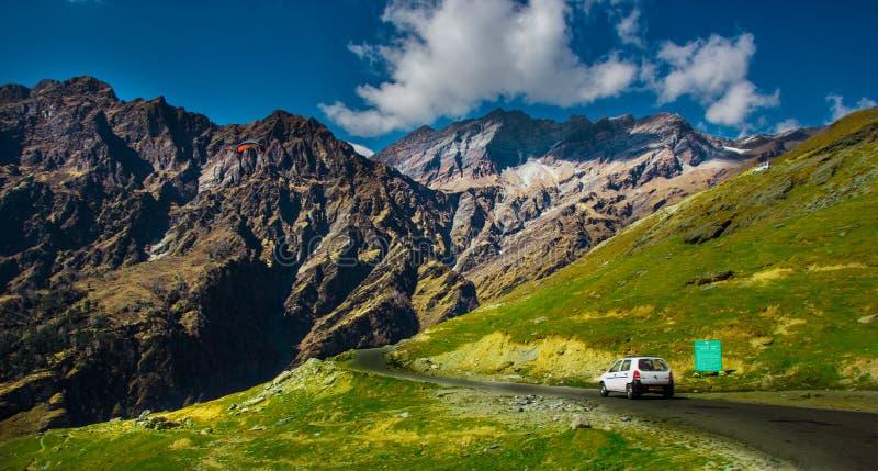 Navigazione di Para accanto alla strada principale collinosa con il pascolo verde ed al cielo blu sul modo in Himalaya dalla stra immagini stock