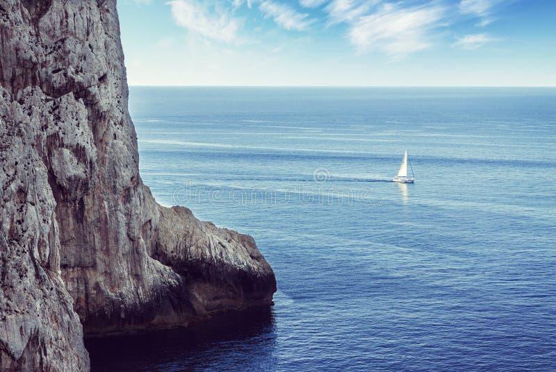 Navigazione sola della barca a vela sul mare fotografia stock
